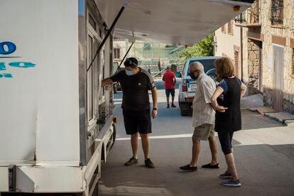 Tres vecinos de Griegos frente a un camión de venta ambulante.