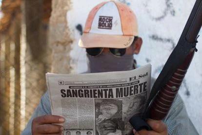 Un hombre del municipio de Ayutla en Guerrero, México, que combate al crimen organizado lee los sucesos en el periódico en una foto de archivo.