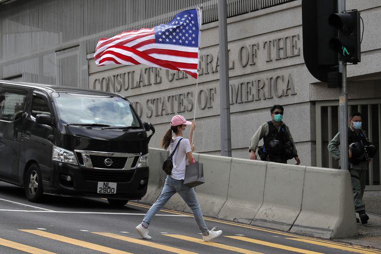Una manifestante lleva una bandera de EE. UU ante el consulado de ese país en Hong Kong, en una protesta en julio pasado