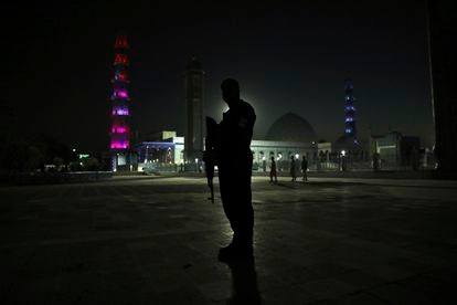 An Afghan policeman in front of the Blue Mosque of Mazar-i-Sharif.