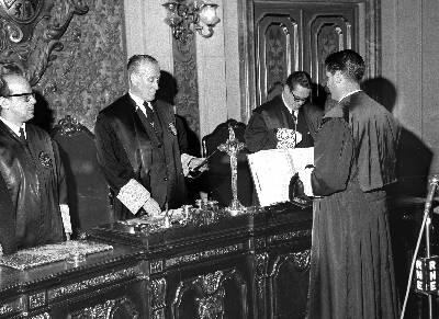 José Francisco Mateu Cánovas (de espaldas) escucha al secretario durante su toma de posesión como presidente del TOP, en 1968. - EFE