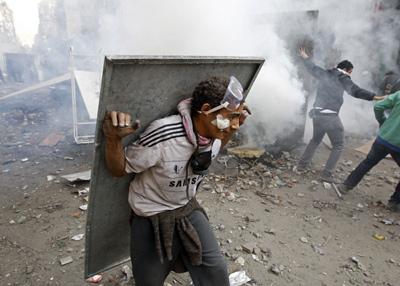 Uno de los manifestantes se protege de las granadas de gases lacrimógenos en una calle lateral de la plaza Tahrir durante los enfrentamientos de ayer. goran tomasevic -REUTERS