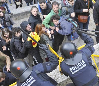 Agentes antidisturbios blanden las porras ante los estudiantes que protestaban hoy en la Universitat de Girona.-