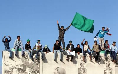 Seguidores del líder libio Muamar el Gadafi sostienen banderas nacionales en la fortaleza de Bab Al Azizia en Trípoli (Libia).