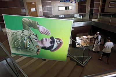 Un rebelde se lleva un retrato de Gadafi de una de las estancias de su complejo presidencial en Bab al Azizia, ayer en Trípoli. -