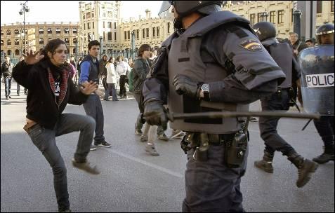 Un agente antidisturbio se dispone a golpear a una joven en el centro de Valencia.