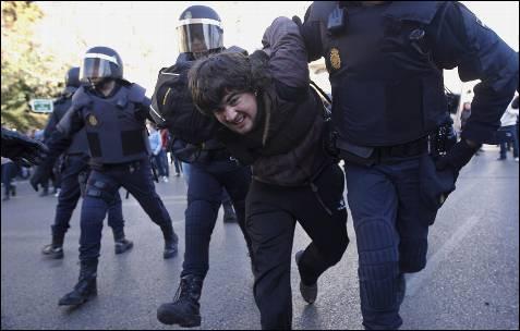 Varios agentes se llevan por la fuerza a un joven.