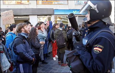 Un antidisturbio se mantiene alerta ante la protesta de los estudiantes.