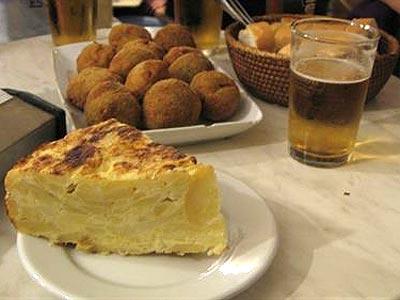 Raciones de tortilla de patatas y croquetas junto a una caña de cerveza en una mesa de un bar. Tnarik (Flickr)