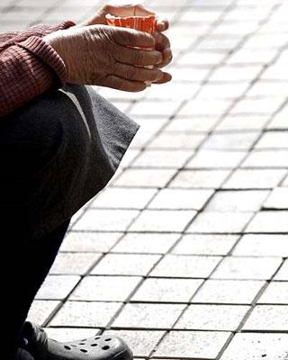 Detalle de las manos de una mujer que pide lismona a las puertas de una iglesia de Valladolid. EFE/Nacho Gallego