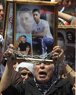 Una mujer palestina muestra la foto de un familiar durante la protesta celebrada en el centro de Naplusa, en Cisjordania. EFE/ALAA BADARNEH