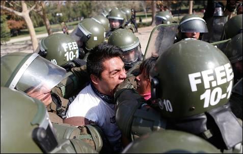 Un manifestante trata de morder a un policía antidisturbios durante una marcha para exigir al Gobierno de Chile la reforma del sistema educativo.