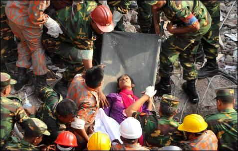Los equipos de rescate trasladan a una mujer, hallada entre los restos del edificio Rana Plaza tras pasar enterrada 17 días entre los escombros. La mujer, identificada como Reshma, está prácticamente ilesa y ha sido localizada en la base del edificio de nueve plantas.