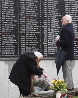 Dos ancianos buscan los nombres de sus difuntos en la Fosa Común del cementerio de San Salvador de Oviedo. ALBERTO MORANTE/ EFE