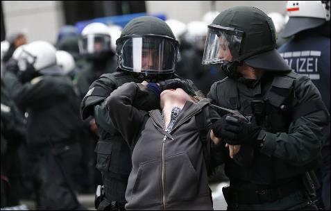 La Policía detiene a una manifestante durante la concentración frente al BCE en Frankfurt organizado por el movimiento Blockupy.
