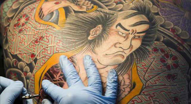Foto de archivo de un hombre tatuándose