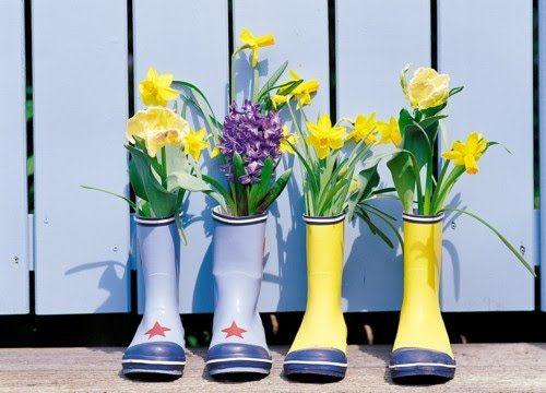 Flores sembradas en botas usadas como macetas