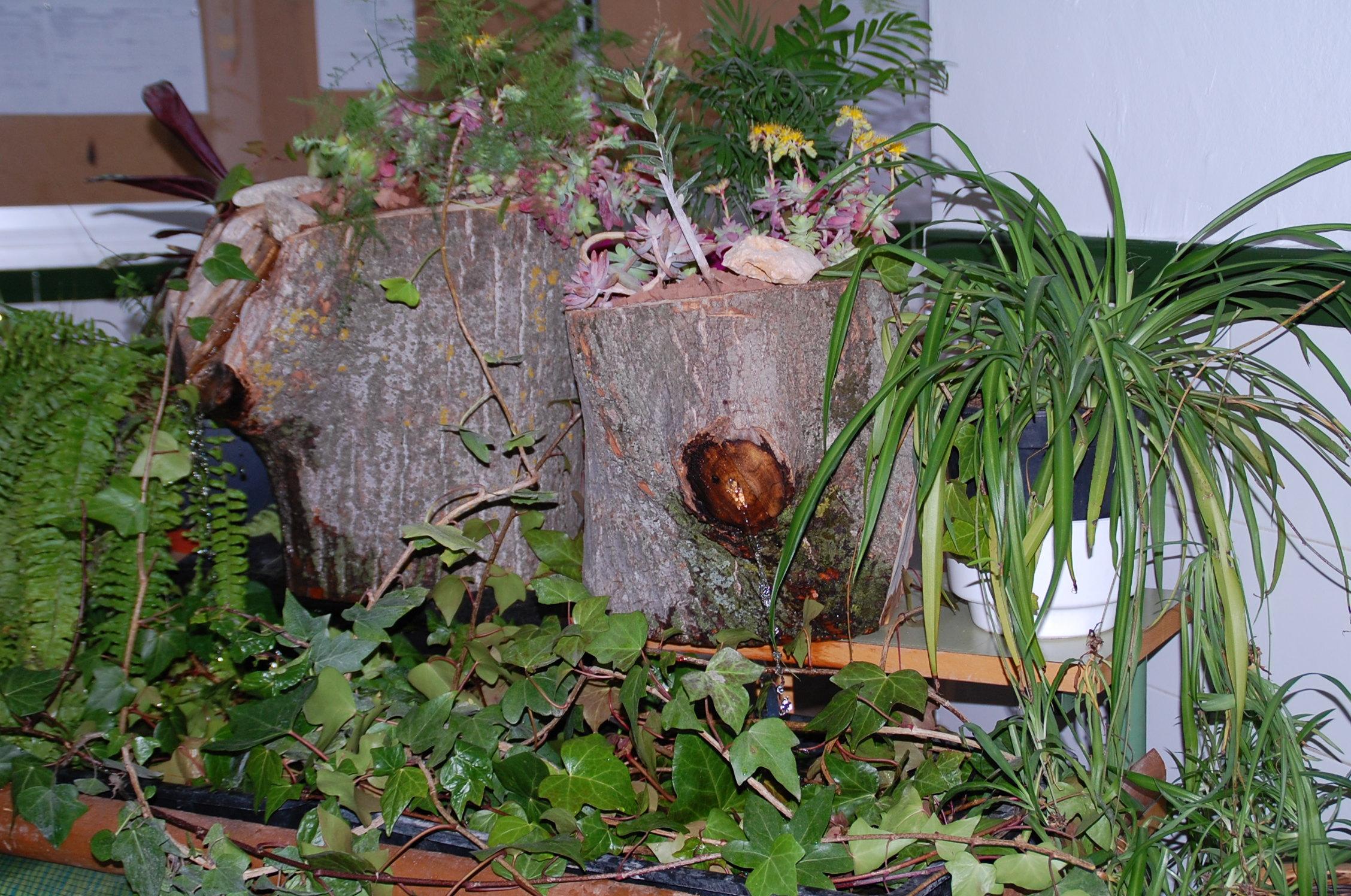 Troncos reciclados con plantas y flores for Como decorar un jardin con plantas