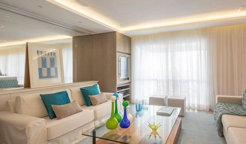 sala planejada pequena com almofadas verdes projeto de Enzo Sobocinski