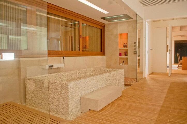 Banheiro de luxo com banheira de pedra Projeto de Toninho Noronha