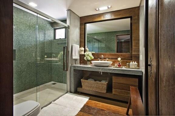 Banheiro de luxo com pastilha verde e revestimento de madeiara Projeto de Gislene Lopes