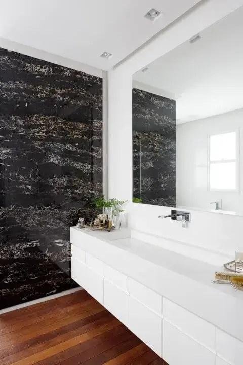 Banheiro de luxo com piso de madeira e revestimento de mármore Projeto de Consuelo Jorge