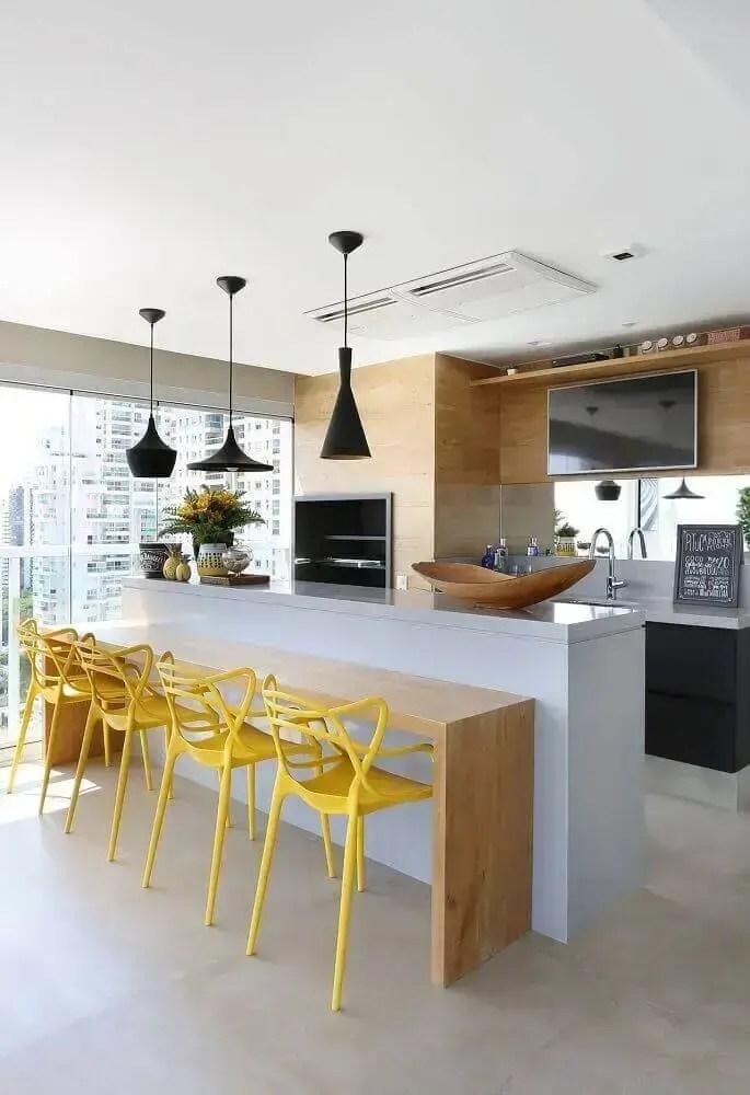 área gourmet moderna com cadeiras amarelas e luminária preta