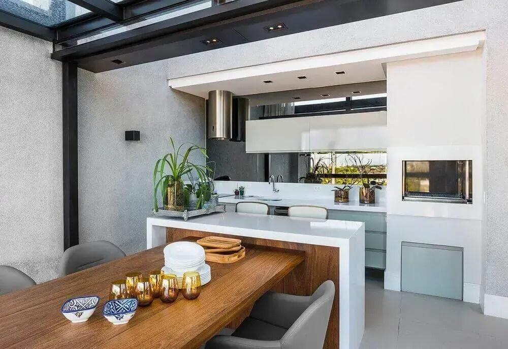 área gourmet moderna com mesa de madeira e poltronas cinza