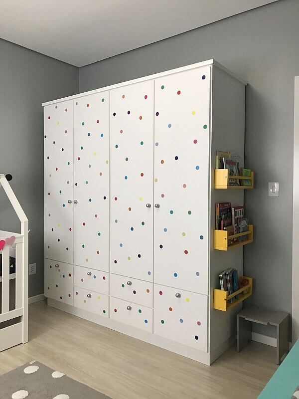 Use colorful stickers to give a special finish to the white 4-door children's wardrobe