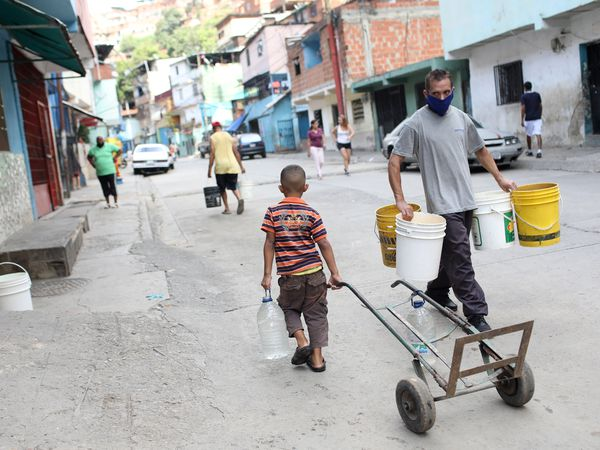 People walk with plastic containers near an unknown water source in the low-income neighbourhood of Petare amid the coronavirus disease (COVID-19) outbreak in Caracas, Venezuela June 3, 2020. Picture taken June 3, 2020. REUTERS/Manaure Quintero