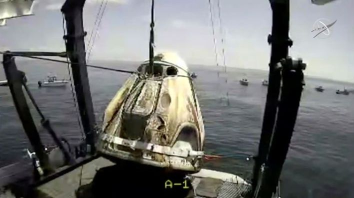 A capsule with NASA astronauts Robert Behnken and Douglas Hurley is lifted out of water in the Gulf of Mexico