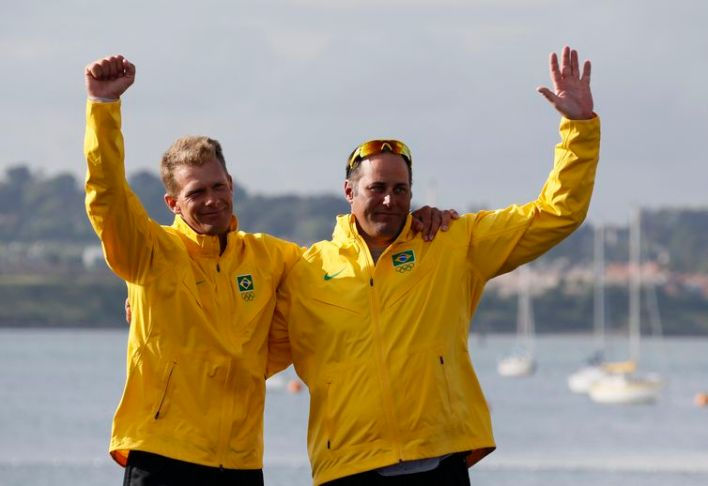 Bronze medallists Brazil's skipper Robert Scheidt and crew Bruno Prada wave during their men's star class keelboat sailing medal race victory ceremony at the London 2012 Olympic Games in Weymouth and Portland
