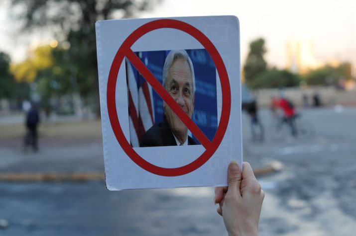 A demonstrator holds up a sign with a picture of Chile's President Sebastian Pinera during a protest against Chile's government at Plaza Italia in Santiago, Chile November 5, 2019. REUTERS/Jorge Silva