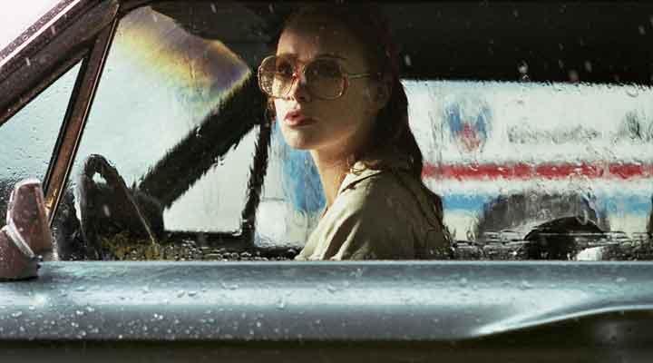 Crítica de Uma Dama De Óculos Escuros Com Uma Arma No Carro