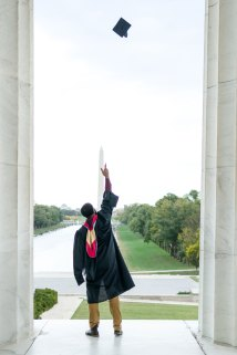 A man poses at the Lincoln Memorial during his graduation session in Washington, D.C.