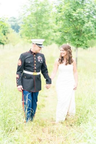 A couple walks through a field during a wedding at Pinehall at Eisler Farm.