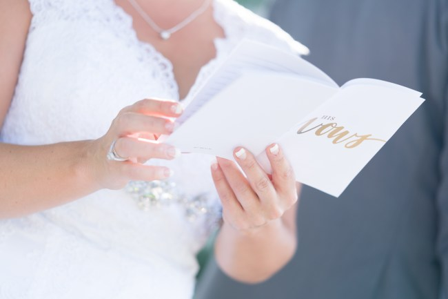 A closeup of a bride reading from a vow book during a wedding at The Citadel in Charleston, SC