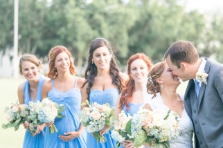 A bride and groom kiss as bridesmaids look on during a wedding at The Citadel.