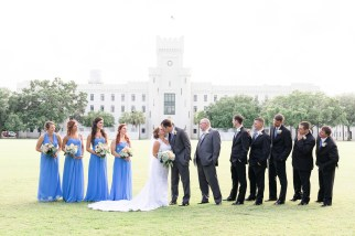 Bridesmaids and groomsmen look at a couple kiss during a wedding at The Citadel in Charleston, SC.