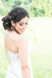 A bride poses underneath a willow tree at The Ospreys at Belmont Bay.