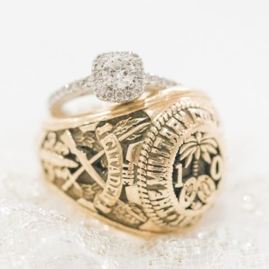 A bride's engagement ring stacked with the groom's class ring from The Citadel.
