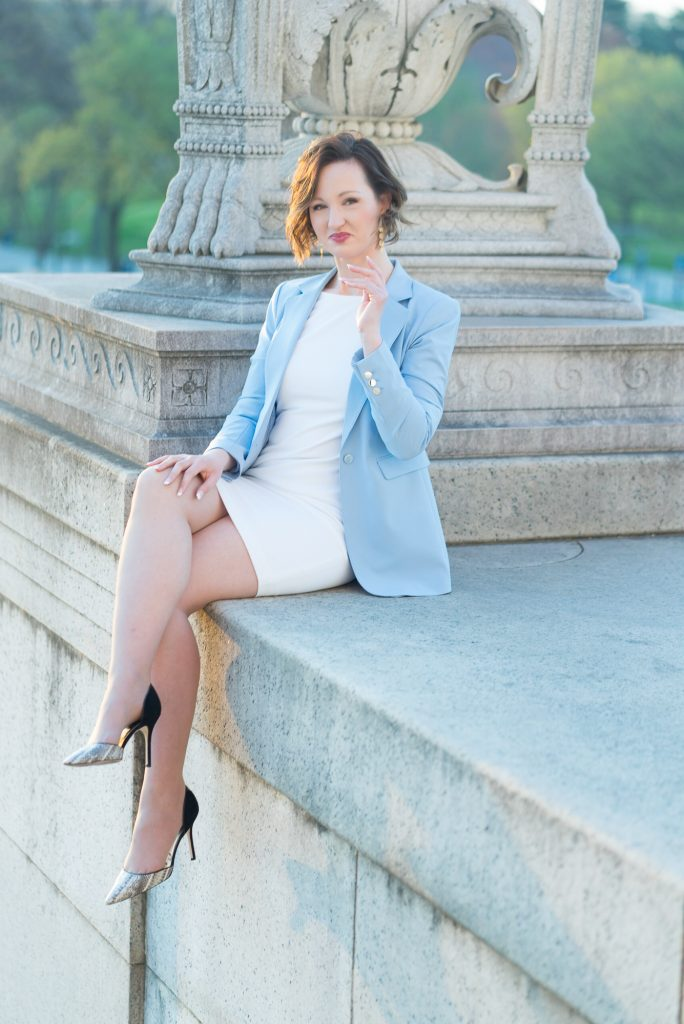 A woman in a light blue blazer poses near the Lincoln Memorial in Washington, D.C. Photography by Erin Julius of Imagery by Erin.