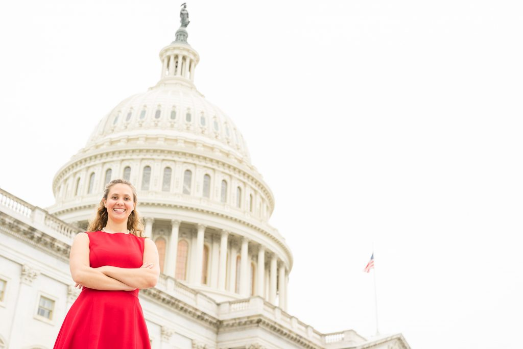 A woman wearing a red dress stands in front of the Capitol