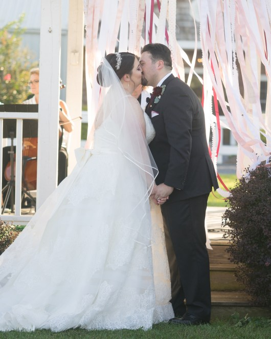 A bride and groom share their first kiss during a ceremony at Hermitage Hill Farm in Waynesboro, Virginia.