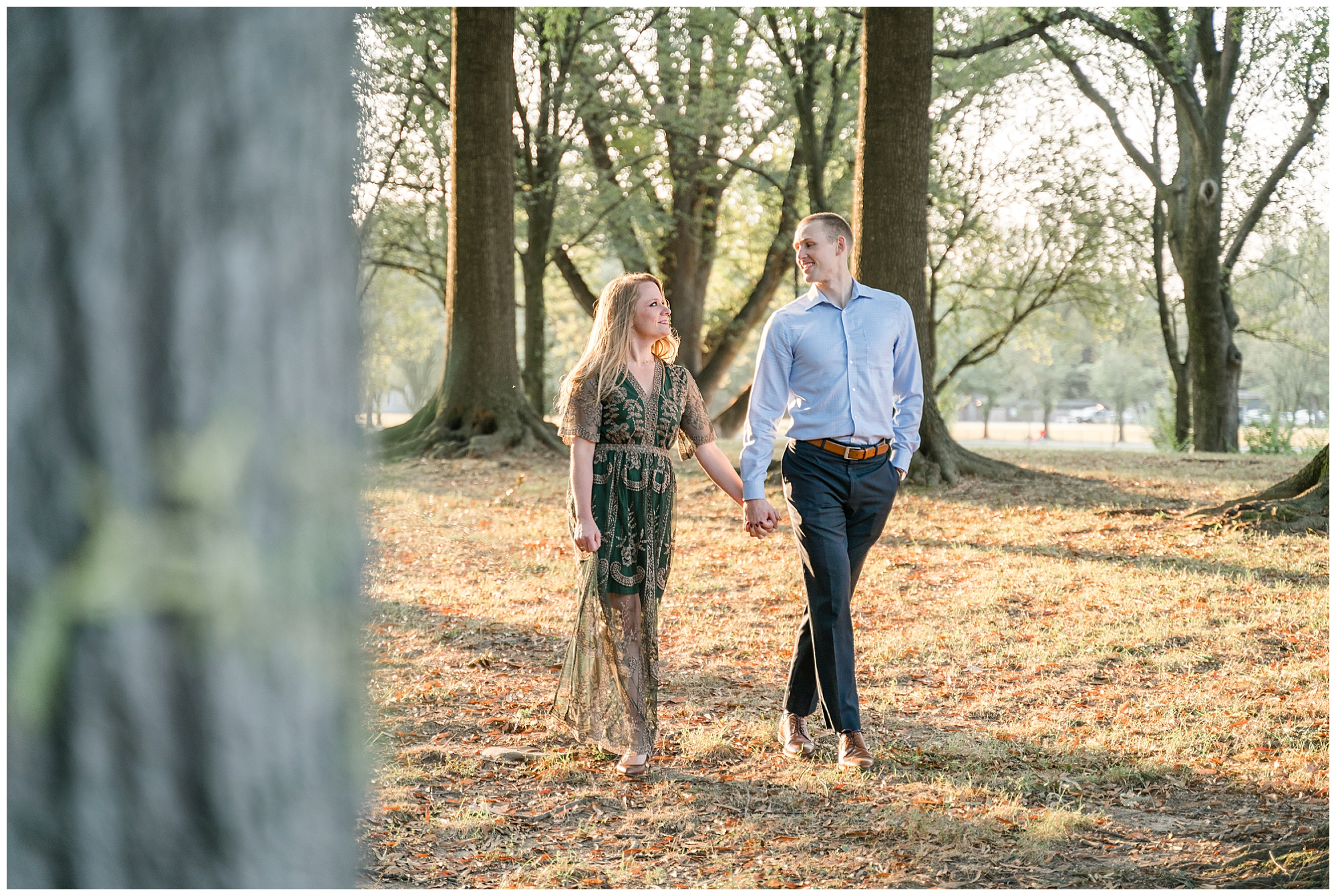 A couple walks through trees while holding hands during their engagement session
