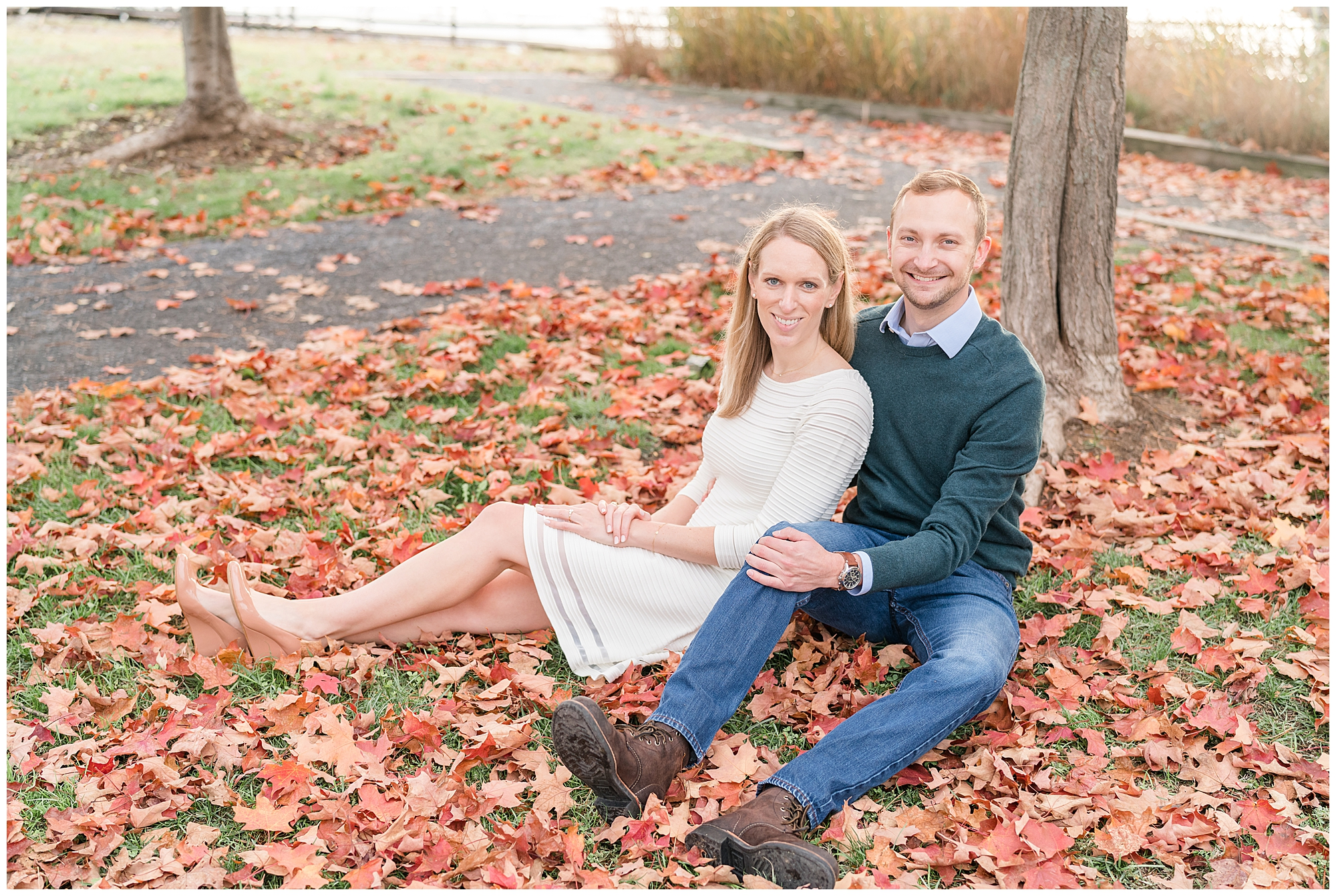 A couple sits in a pile of fallen red leaves during their Alexandria VA engagement session.