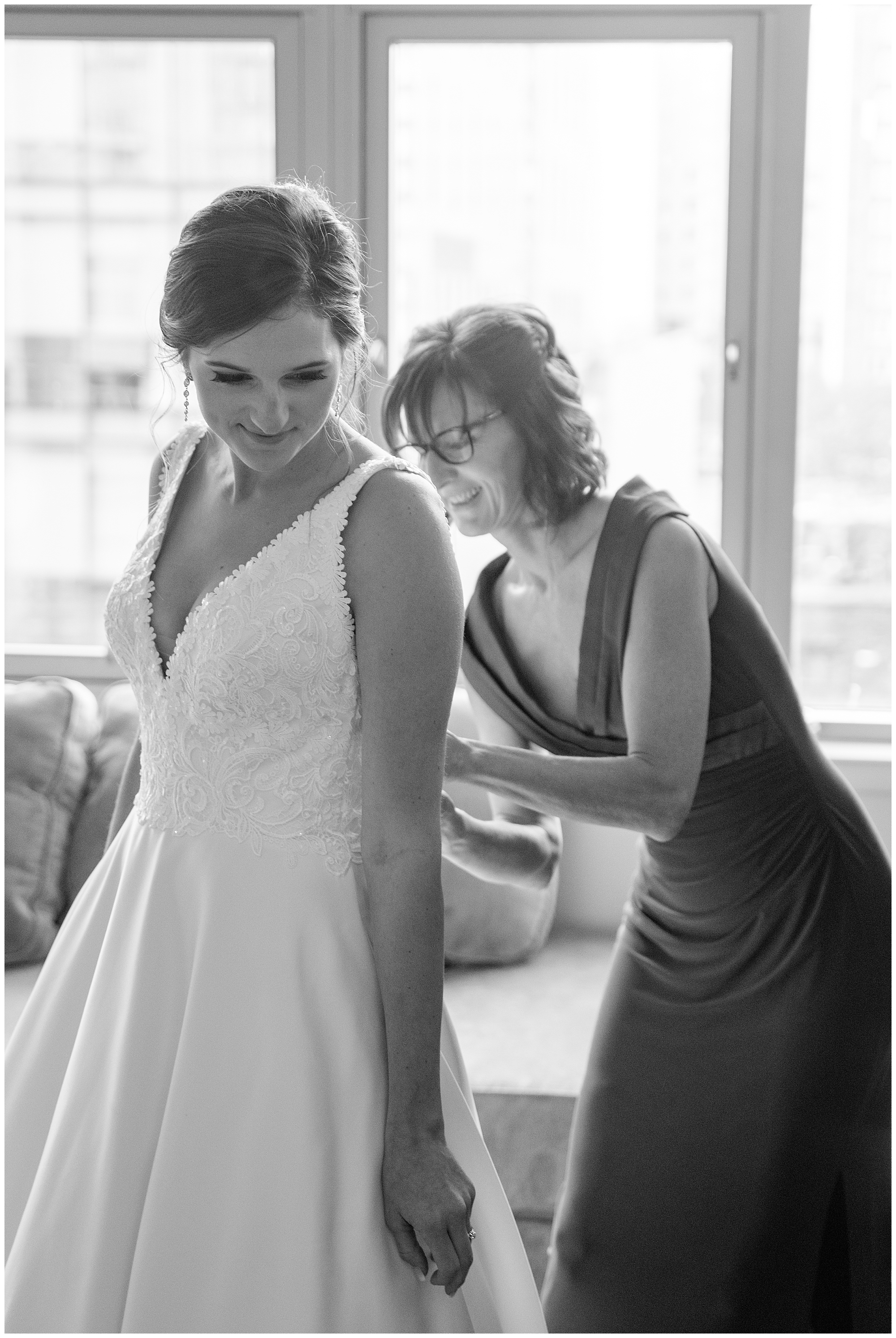 A black and white photo of a mother zipping up her daughter's dress before her Washington DC wedding.