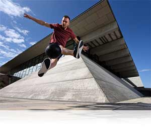 Nikon D750 photo of a male parkour athlete in mid air jump showing speed of the camera