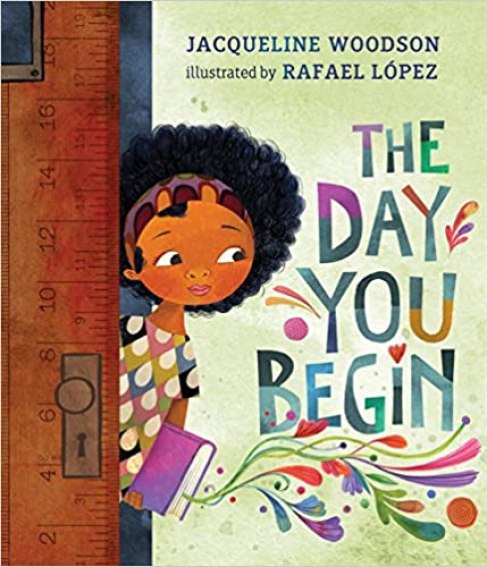 An image of a young Caribbean girl.  She is peeking through a wooden door, about to enter a room.  She is wearing a cloth headband in her hair, a colorful, patterned shirt and dark pants.  There is a purple book in her hand.