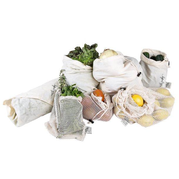 Bolsas de mesh y algodón orgánico para hacer compras de la marca Earth Junky llenas de frutas y verduras.